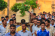 Syrians carry the body of 70-year-old Amina Ahmed Kabso at a cemetery in Tall Rifat village near Aleppo on Saturday, June 23, 2012. Kabso was killed in the latest spate of violence in northern Syria. Kabso was reportedly killed while traveling from Aleppo to her home in Tall Rifat when Syrian security forces targeted the mini-bus she was in. (Photo by Vudi Xhymshiti)