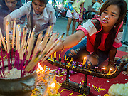"07 MARCH 2015 - NAKHON CHAI SI, NAKHON PATHOM, THAILAND: A family lights candles to make merit during the Wat Bang Phra tattoo festival. Wat Bang Phra is the best known ""Sak Yant"" tattoo temple in Thailand. It's located in Nakhon Pathom province, about 40 miles from Bangkok. The tattoos are given with hollow stainless steel needles and are thought to possess magical powers of protection. The tattoos, which are given by Buddhist monks, are popular with soldiers, policeman and gangsters, people who generally live in harm's way. The tattoo must be activated to remain powerful and the annual Wai Khru Ceremony (tattoo festival) at the temple draws thousands of devotees who come to the temple to activate or renew the tattoos. People go into trance like states and then assume the personality of their tattoo, so people with tiger tattoos assume the personality of a tiger, people with monkey tattoos take on the personality of a monkey and so on. In recent years the tattoo festival has become popular with tourists who make the trip to Nakorn Pathom province to see a side of ""exotic"" Thailand.   PHOTO BY JACK KURTZ"