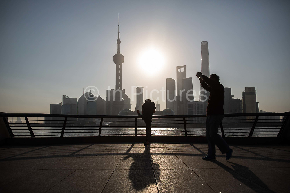 People exercise and walk along the Bund while buildings of Pudongs Lujiazui financial district stand across the Huangpu River as the sun rises in Shanghai, China, on Friday, Oct. 2, 2015.