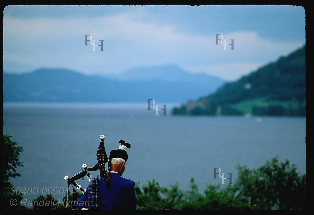 Bagpiper serenades waters of Loch Ness near Urquhart Castle on a July morning; Drumnadrochit. Scotland
