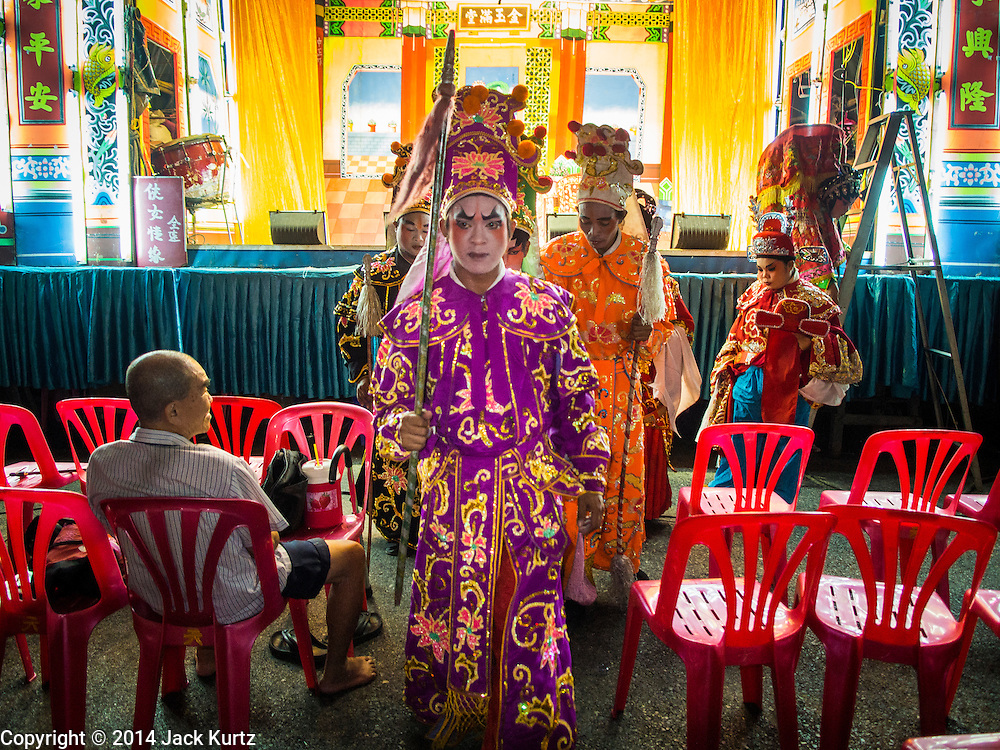 """18 AUGUST 2014 - BANGKOK, THAILAND:   Members of the Lehigh Leng Kaitoung Opera troupe walk through the crowd to the shrine at the beginning of a performance at Chaomae Thapthim Shrine, a small Chinese shrine in a working class neighborhood of Bangkok. The performance was for Ghost Month. Chinese opera was once very popular in Thailand, where it is called """"Ngiew."""" It is usually performed in the Teochew language. Millions of Chinese emigrated to Thailand (then Siam) in the 18th and 19th centuries and brought their culture with them. Recently the popularity of ngiew has faded as people turn to performances of opera on DVD or movies. There are still as many 30 Chinese opera troupes left in Bangkok and its environs. They are especially busy during Chinese New Year and Chinese holiday when they travel from Chinese temple to Chinese temple performing on stages they put up in streets near the temple, sometimes sleeping on hammocks they sling under their stage. Most of the Chinese operas from Bangkok travel to Malaysia for Ghost Month, leaving just a few to perform in Bangkok.      PHOTO BY JACK KURTZ"""