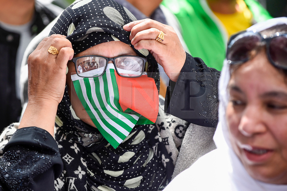 © Licensed to London News Pictures. 15/08/2019. LONDON, UK.  A woman covers her face in a flag as thousands of protesters, many waving Pakistani and Kashmiri flags, gather outside the Indian High Commission in Aldwych, on what they are calling Black Day, to stand in solidarity with the people of Kashmir.  Indian Prime Minister Narendra Modi delivered an Independence Day speech highlighting his decision to remove the special rights of Kashmir as an autonomous region.  Photo credit: Stephen Chung/LNP