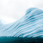 A blue iceberg with deeply etched grooves lies in the waters off Melchior Island on the western side of the Antarctic Peninsula. The grooves are caused by compressed air bubbles escaping as the iceberg slowly melts.