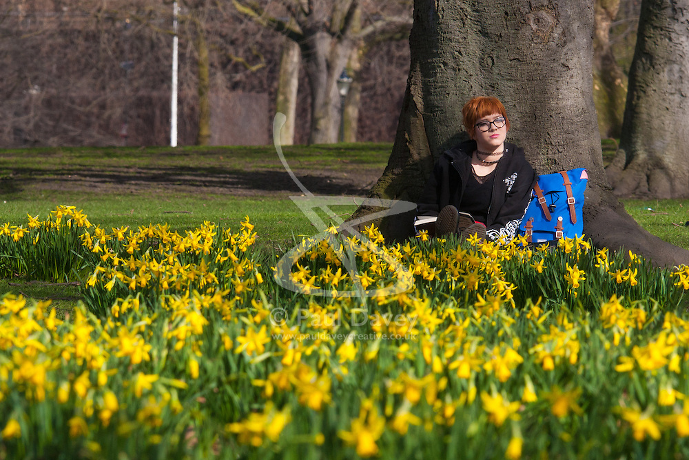 London, March 6th 2015. Londoners and tourists enjoy the warm sunshine in St James's Park as daffodils bloom, heralding the approach of spring. PICTURED: Eighteen-year-old Ellen Oort, visiting London from Queensland in Australia relaxes amongst the daffodils as the sun warms her face.
