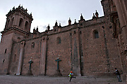 TWO BOYS PLAYING SOCCER OUTSIDE THE CATHEDRAL OF CUSCO IN PERU.