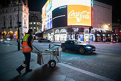 © Licensed to London News Pictures. 20/03/2020. London, UK. A street cleaner moves his cart across Piccadilly Circus. The West End was left unprecedentedly empty on Friday night following the government's announcement that all bars, pubs and restaurants must be closed immediately in the latest step to curb the coronavirus outbreak.  Photo credit: Guilhem Baker/LNP