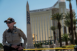 October 3, 2017 - Las Vegas, Nevada, U.S - A Las Vegas Police officer stands near yellow police tape on Las Vegas Boulevard near the Mandalay Hotel and the site of Sunday's mass shooting which claimed the lives of 59 people and injured hundreds of others. (Credit Image: © Nick Otto via ZUMA Wire)