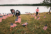 10 SEPTEMBER 2020 - DES MOINES, IOWA: About 25 volunteers braved cold and rainy weather Thursday to line the west end of Gray's Lake in Des Moines with American flags. The display of the flags was a part of an annual event called the 9/11 Tribute Trail. About 3,000 flags were set out in memorial of the 3,000 people killed in the 9/11 terrorist attacks.     PHOTO BY JACK KURTZ