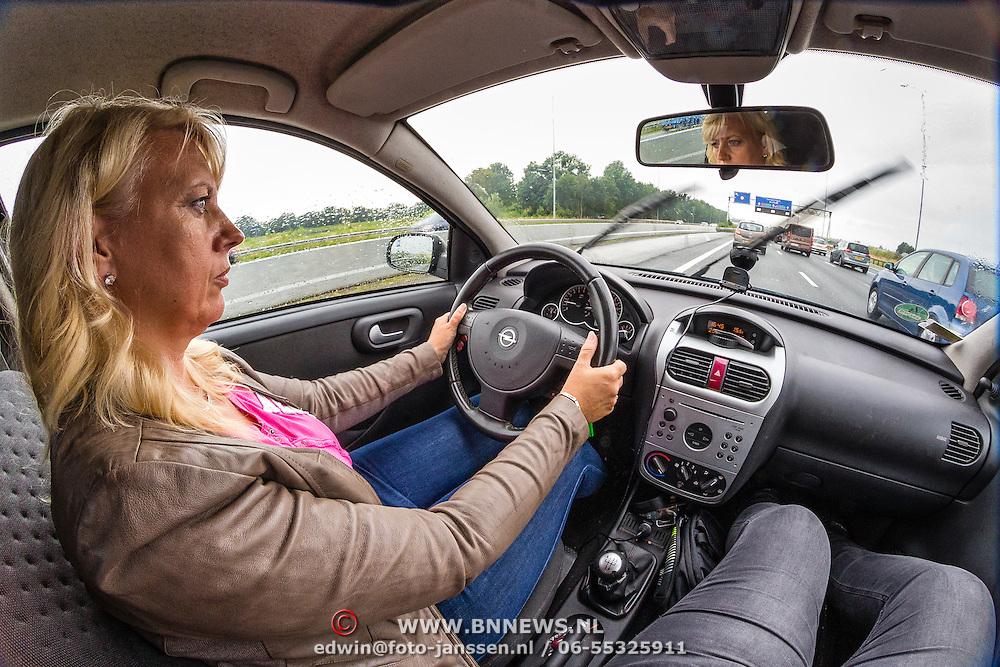 NLD/Amsterdam/20160625 - Vrouw rijdend in haar auto,