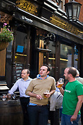 Young men drink beer outside the Salisbury, a Victorian era public house in the Covent Garden area of London, UK