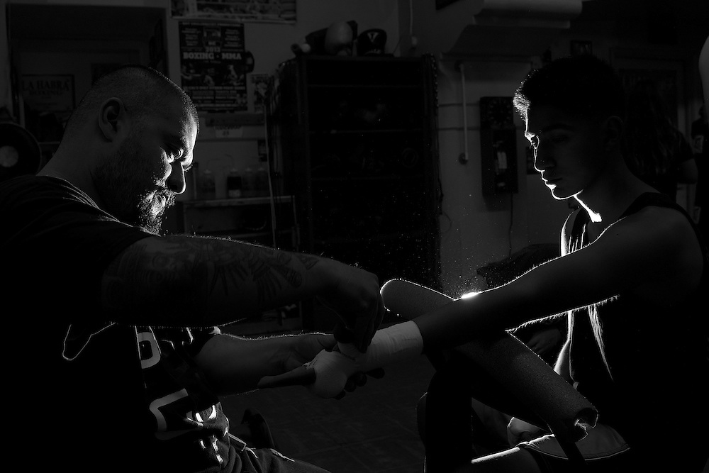 November 3rd, 2016; La Habra, California, USA; A trainer works to tape a boxer's gloves before a sparring session at the La Habra Boxing Club. (Eric Cech/Sports Shooter Academy)