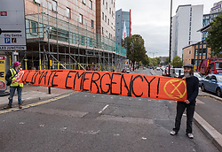 © Licensed to London News Pictures. 08/10/2018. Bristol, UK. Activists block the main road of Marlborough Street at the 'Extinction Rebellion' campaign event 'Make Ecocide Law' about the threat of climate change, at Bristol Magistrates Court and Marlborough Street. The Extinction Rebellion campaign wants to make ecocide a crime in UK law, saying the threat of climate change threatens the lives of millions of people on the planet. The campaign is organised by Rising Up, and the event happened on the day that the Intergovernmental Panel on Climate Change (IPCC) has issued a special report on the impact of global warming of 1.5C. Campaigners used removable chalk spray to write on the windows of Bristol Magistrates Court, and blocked the main road before being removed by police. There were three arrests. Rising Up plans more actions in November. Photo credit: Simon Chapman/LNP