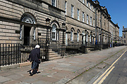 An elderly lady walks along Charlotte Square in Edinburgh, on 26th June 2019, in Edinburgh, Scotland.