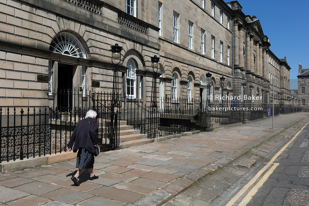 An elderly lady walks along Charlotte Square in Edinburgh, on 26th June 2019, in Edinburgh, Scotland.