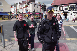 Group of homeless teenagers walking together through seaside town centre,