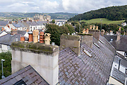 Seen from the ramparts of medieval Conwy castle are the rooftops of homes within its fortified walls, on 4th October 2021, in Conwy, Gwynedd, Wales. The walls were constructed between 1283 and 1287 after the foundation of Conwy by Edward I, and were designed to form an integrated system of defence alongside Conwy Castle. The walls are 1.3 km 0.81 mi long and include 21 towers and three gatehouses. Conwy is a walled market town and community on the north coast of Wales.
