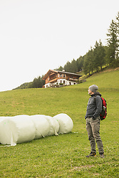 Mature hiker standing near bales and looking at view, Austrian alps, Carinthia, Austria