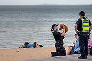 A police officer is seen cuddling a puppy on St Kilda Beach during COVID-19 in Melbourne, Australia. Premier Daniel Andrews comes down hard on Victorians breaching COVID 19 restrictions, threatening to close beaches if locals continue to flout the rules. This comes as Victoria sees single digit new cases. (Photo by Dave Hewison/Speed Media)