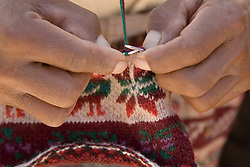 Knitting traditional wool hat (close-up of hands), Taquile Island (also known as Isla Taquile), Lake Titicaca, Peru, South America