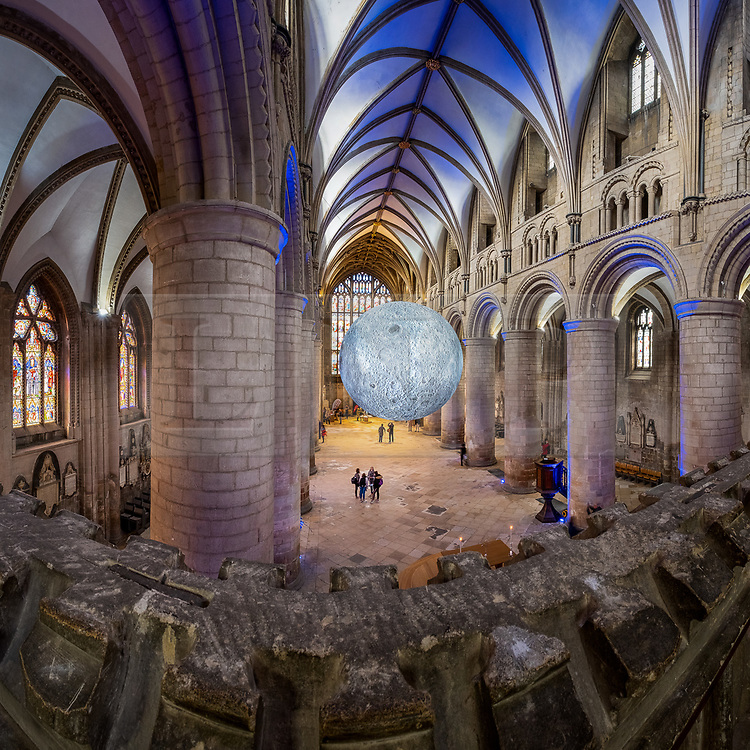 """© Licensed to London News Pictures 16/10/2019, Gloucester, UK. First day of """"The Museum of the Moon"""" a touring artwork by artist Luke Jerram, displaying a 3D replica of the Moon, internally lit and floating in the Nave of Gloucester Cathedral. The lunar imagery is accompanied by immersive surround sound composed by BAFTA award winner, Dan Jones. This photohgraoh is a composite of 5 shots stitched to gether to make the final panorama. Photo Credit : Stephen Shepherd/LNP"""