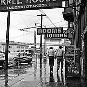 Two pedestrians walking down rainy Embarcadero, San Francisco