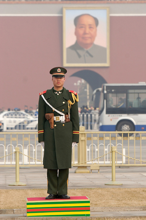 A soldier stands guard at the North side of Tiananmen Square across the street from the southern entrance to the Forbidden City which holds a large portrait of Chairman Mao in Beijing, China.