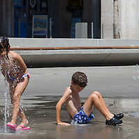 Children cool down in the summer heat in the fountains of a public park in downtown Budapest, Hungary on July 19, 2015. ATTILA VOLGYI