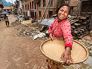 04 AUGUST 2015 - KHOKANA, NEPAL: A woman in a street clogged with earthquake debris in Khokana, a village about an hour from Kathmandu. Three months after the earthquake, roads in many rural villages are still blocked by earthquake debris. The Nepal Earthquake on April 25, 2015, (also known as the Gorkha earthquake) killed more than 9,000 people and injured more than 23,000. It had a magnitude of 7.8. The epicenter was east of the district of Lamjung, and its hypocenter was at a depth of approximately 15 km (9.3 mi). It was the worst natural disaster to strike Nepal since the 1934 Nepal–Bihar earthquake. The earthquake triggered an avalanche on Mount Everest, killing at least 19. The earthquake also set off an avalanche in the Langtang valley, where 250 people were reported missing. Hundreds of thousands of people were made homeless with entire villages flattened across many districts of the country. Centuries-old buildings were destroyed at UNESCO World Heritage sites in the Kathmandu Valley, including some at the Kathmandu Durbar Square, the Patan Durbar Squar, the Bhaktapur Durbar Square, the Changu Narayan Temple and the Swayambhunath Stupa. Geophysicists and other experts had warned for decades that Nepal was vulnerable to a deadly earthquake, particularly because of its geology, urbanization, and architecture.     PHOTO BY JACK KURTZ