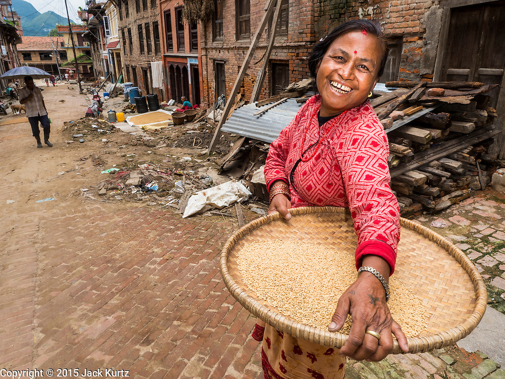 04 AUGUST 2015 - KHOKANA, NEPAL: A woman in a street clogged with earthquake debris in Khokana, a village about an hour from Kathmandu. Three months after the earthquake, roads in many rural villages are still blocked by earthquake debris. The Nepal Earthquake on April 25, 2015, (also known as the Gorkha earthquake) killed more than 9,000 people and injured more than 23,000. It had a magnitude of 7.8. The epicenter was east of the district of Lamjung, and its hypocenter was at a depth of approximately 15km (9.3mi). It was the worst natural disaster to strike Nepal since the 1934 Nepal–Bihar earthquake. The earthquake triggered an avalanche on Mount Everest, killing at least 19. The earthquake also set off an avalanche in the Langtang valley, where 250 people were reported missing. Hundreds of thousands of people were made homeless with entire villages flattened across many districts of the country. Centuries-old buildings were destroyed at UNESCO World Heritage sites in the Kathmandu Valley, including some at the Kathmandu Durbar Square, the Patan Durbar Squar, the Bhaktapur Durbar Square, the Changu Narayan Temple and the Swayambhunath Stupa. Geophysicists and other experts had warned for decades that Nepal was vulnerable to a deadly earthquake, particularly because of its geology, urbanization, and architecture.     PHOTO BY JACK KURTZ