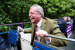 © Licensed to London News Pictures. 25/05/2016. Chapeltown, UK. Nigel Farage ducks to avoid overhanging trees as he rides atop the UKIP Referendum open top bus in Chapeltown, South Yorkshire. The party's purple open top battle bus is touring the country in the run up to the EU referendum. There is just a month to go until the UK's referendum on it's membership of the European Union. Poll stations will open their doors on Thursday 23 June. Photo credit : Ian Hinchliffe/LNP