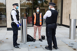London, UK. 10 November, 2020. Metropolitan Police officers temporarily detain an environmental activist from Extinction Rebellion outside the Shell Centre on the 25th anniversary of the killings of the Ogoni Nine. The Ogoni Nine, leaders of the Movement for the Survival of the Ogoni People (MOSOP), were executed by the Nigerian government in 1995 after having led a series of peaceful marches involving an estimated 300,000 Ogoni people against the environmental degradation of the land and waters of Ogoniland by Shell and to demand both a share of oil revenue and greater political autonomy.