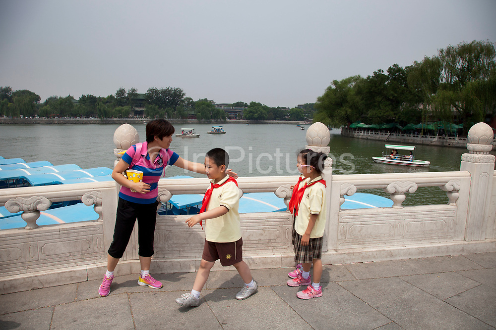 School children walking across the bridge in Beihai Park is an imperial garden in Beijing. First built in the 10th century, it is amongst the largest of Chinese gardens, and contains numerous historically important structures, palaces and temples. Since 1925, the place has been open to the public as a park. It is also connected at the south to the Shichahai. The Park has an area of more than 69 hectares, with a lake that covers more than half of the entire Park.