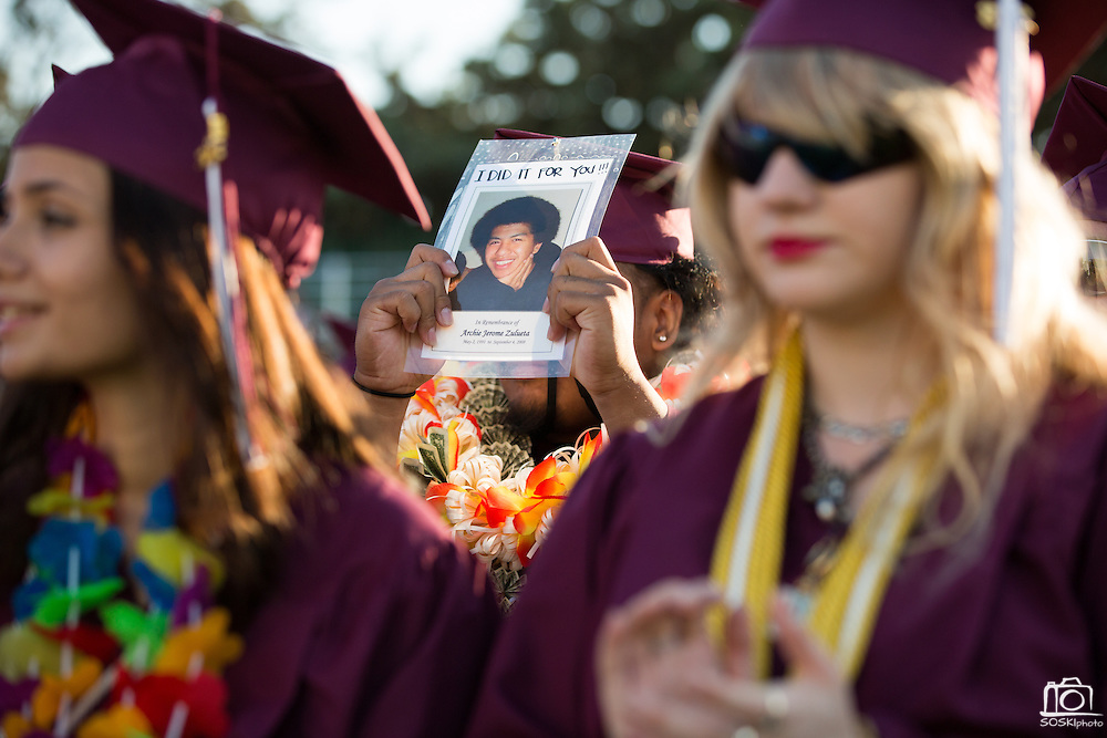 Djeremy Zulueta holds up a photo in memoriam of his brother Archie Jerome Zulueta during the Class of 2013 graduation at the Milpitas Sports Center in Milpitas, California, on June 6, 2013. (Stan Olszewski/SOSKIphoto)