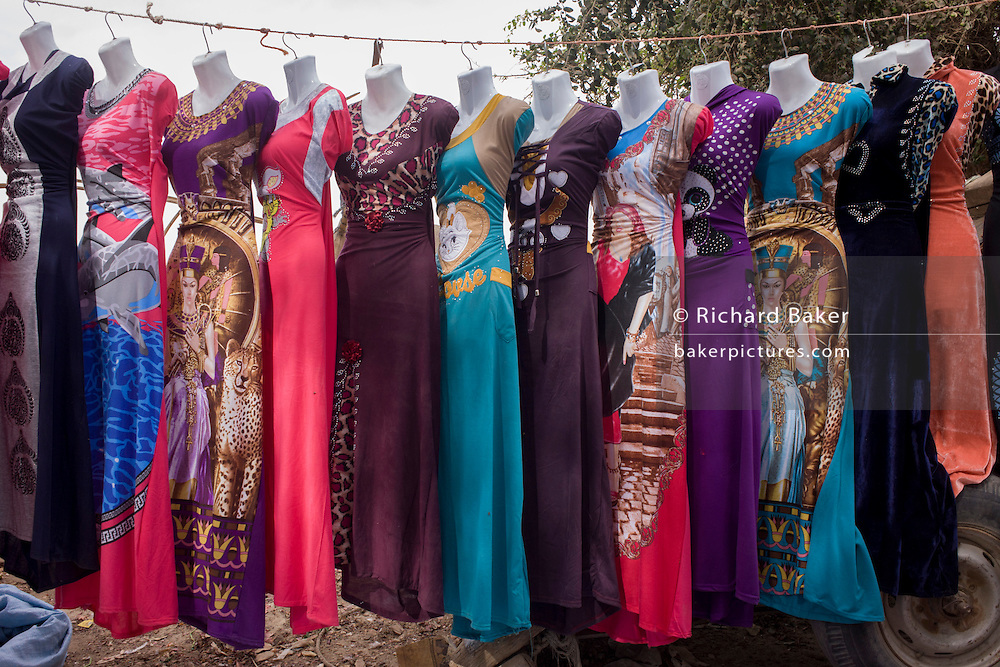 Colourful dress designs hang from a line on a stall at the weekly market at Qurna, a village on the West Bank of Luxor, Nile Valley, Egypt.