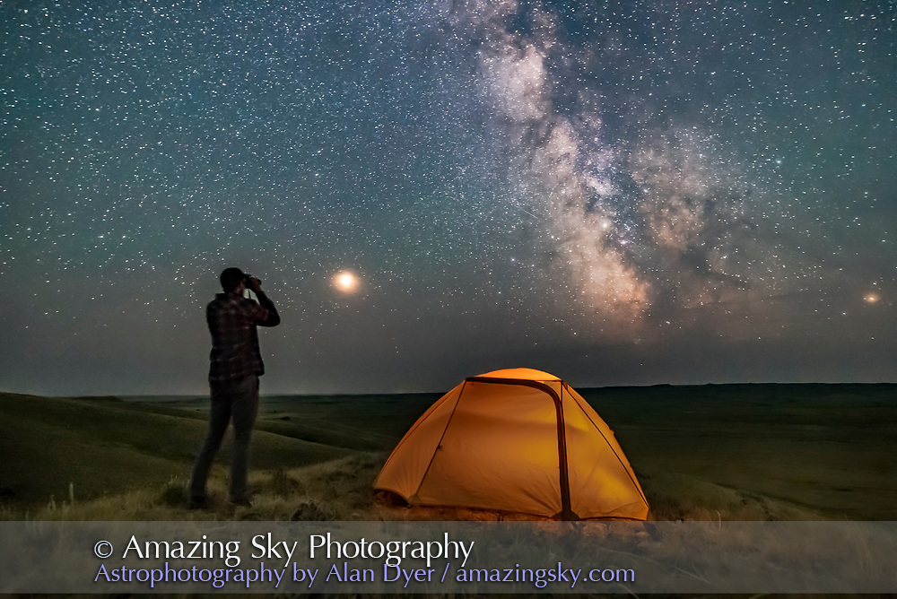 A Park interpreter poses for a scene in Grasslands National Park, Saskatchewan, of stargazing with binoculars under the Milky Way on a dark moonless night. Grasslands is perfect for stargazing as it is a Dark Sky Preserve and the horizon is vast and unobstructed. <br /><br />Mars is bright to the left and the galactic centre is to the south at right. The view is overlooking the Frenchman River Valley. <br /><br />This is a stack of 4 exposures for the ground and one untracked exposure for the sky, all 30 seconds at f/2.8 with the 20mm Sigma lens and Nikon D750 at ISO 6400. LENR was on.
