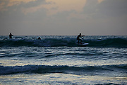 Silhouette of sup surfers in the Mediterranean sea. Photographed in Tel Aviv at sunset