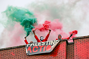 """Palestine Action activists light flares as they hold a banner """"Palestine Action"""" after they scaled the roof of """"Cairo House"""" in Oldham on Monday, June 21, 2021. This is the ongoing protest forms of the human rights activists group in Britain targeting an Israeli owned weapons manufacturer Elbit Systems. Activists argue that arms being manufactured in the facility are being used in indiscriminate attacks against the Gaza Strip. (VX Photo/ Vudi Xhymshiti)"""