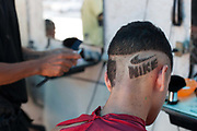 Brazilian youth young man having a Nike logo shaved cut into the back of his hair head. Young independent barber shop hair stylist in the street for the young people guys of Vila Valquiere, West Zone Zona Oueste, Rio de Janeiro