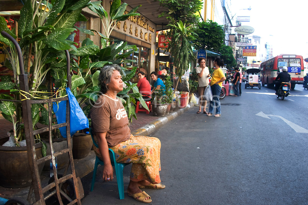 Woman sits quietly in the street. Bangkok's bustling Chinatown (Sampeng) has an almost more authentic old China atmosphere and visual appearance than much of China itself. A compact area of shops Chinese signage, market stalls, food, transport workers and crowds, this area is in distinct contrast to Thai areas. Alleyways, narrow streets all fit together and are lined by shop-houses.