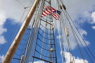 An early American Flag, mast and rigging against a deep blue cloudy sky during the Perry 200 Commemoration, September 2013, Erie Pennsylvania, USA