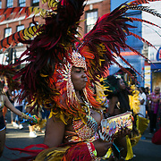 A woman in a red and yellow feather costume dances along pouting her lips, drink in hand, in East London, United Kingdom,Sept 11 2016. The annual Hackney Carnival took place on a hot summers day and the procession of dancers dressed in various outfits moved through the streets to much joy of the many bystanders.