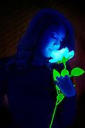 Woman smelling a glowing flower.Black light