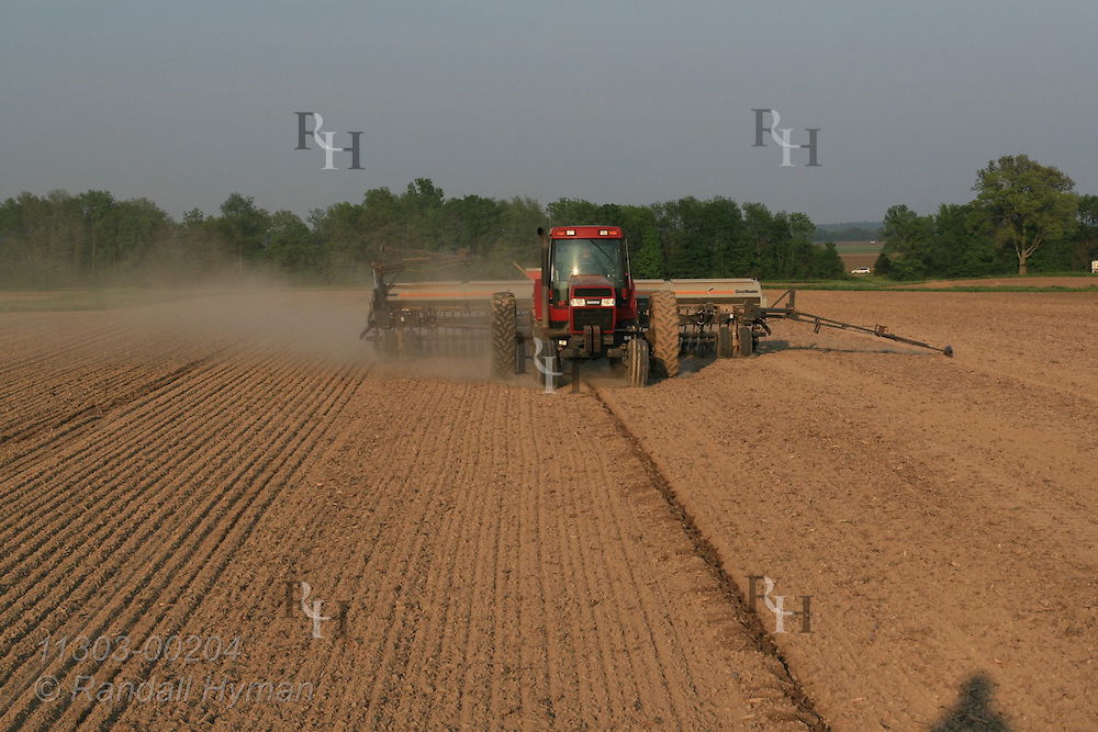 Farmer drives tractor across field planting soybeans with drill attachment; West Union, Illinois.