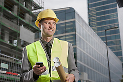 Happy site manager holding blueprints and mobile standing at a construction site