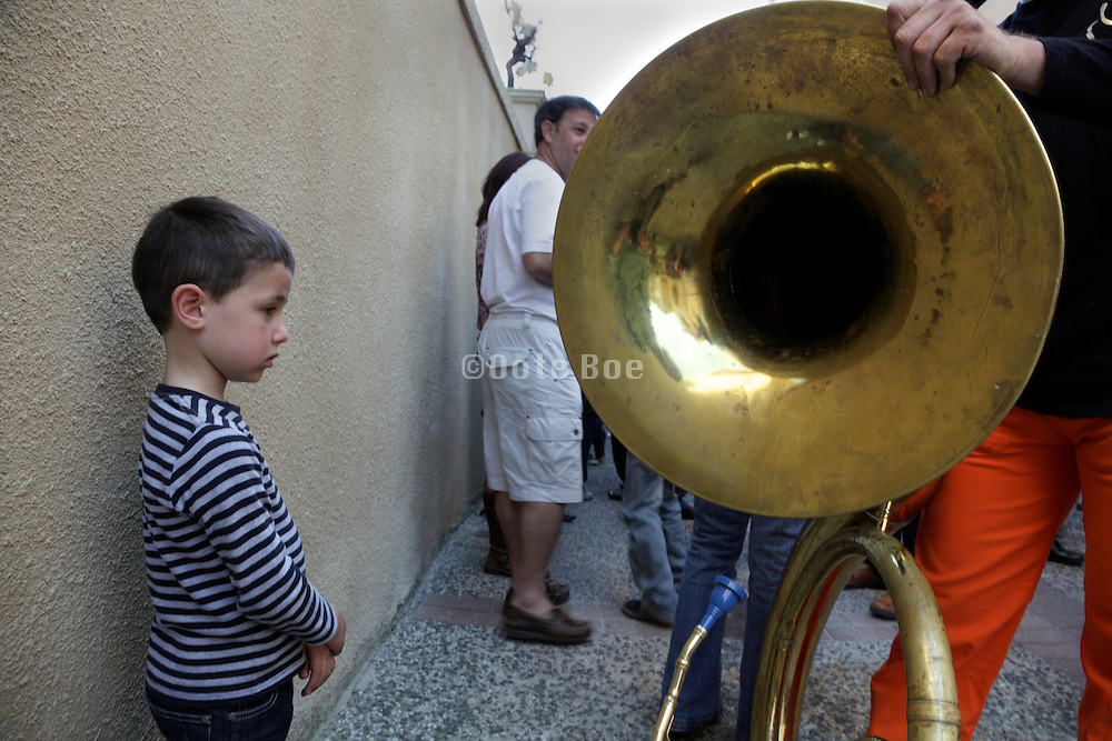 little boy looking at a large tuba at a street festival
