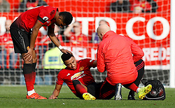 Manchester United's Jesse Lingard (second right) receives medical attention after going down injured during the Premier League match at Old Trafford, Manchester.