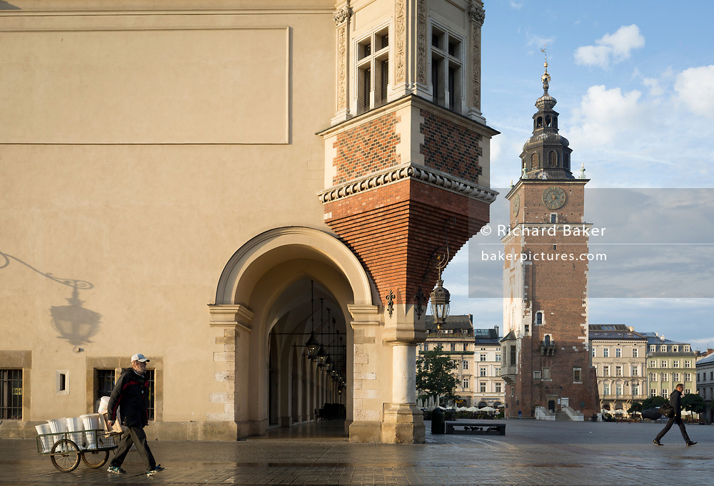 A flower seller pulls his cart to refill fresh water from a nearby tap and past the architecture of the Cloth Hall and the the City Hall Tower (right) on Rynek Glowny market square, on 23rd September 2019, in Krakow, Malopolska, Poland.
