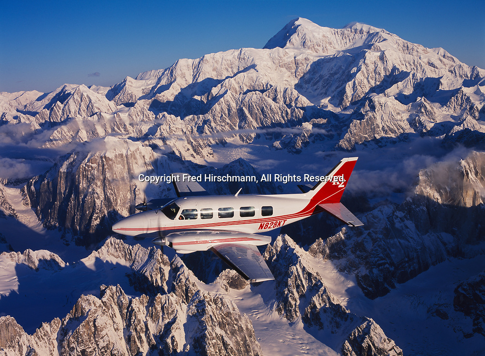 K2 Aviation's Piper Navajo Chieftain flying on the east side of Ruth Gorge with Mount McKinley or Denali beyond, Denali National Park, Alaska.