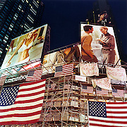 Times Square ads, Manhattan. Patriotic Americana - After 9/11. Advertising bllboard hoardings and American flags in Times Square, NYC. In the week after the September 11th attacks, America sought to express their anger and patriotic unity. Flags and ads adorn a construction site in Times Square...