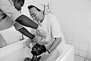 Jeffrey Tembo from the Mepipe Village near Lusaka Zambia, 26, is given a bath by Sister Leonia and attendant at the Mother of Mercy Hospice in Chilanga, Zambia which provides palliative care for those afflicted with AIDS.